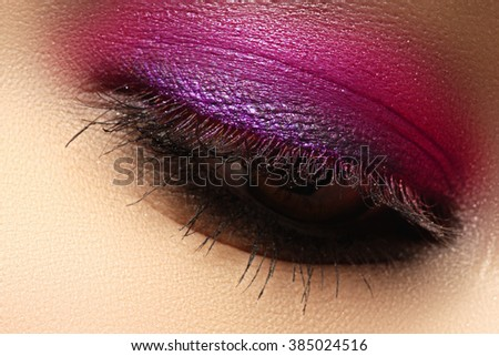 Beautiful macro shot of female eye with creative makeup. Bright colorful makeup. Cosmetics and make-up. Closeup macro shot of fashion sparcle visage