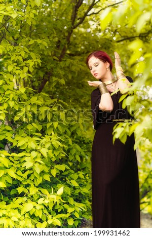 Beautiful makeup girl wearing black tunic and an antique jewels, green leaves on background - stock photo