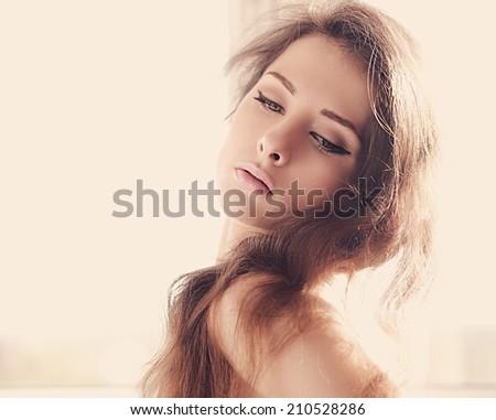 Beautiful makeup woman looking down. Art portrait of woman in sun light - stock photo