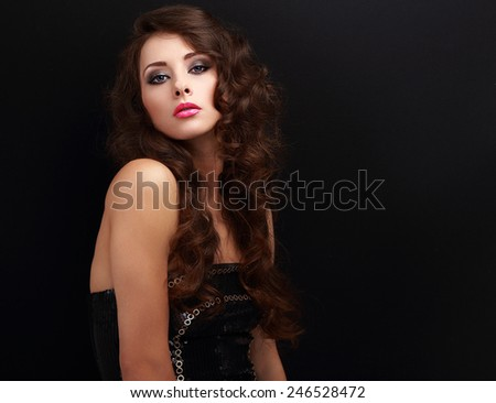 Beautiful makeup woman with long curly hair looking in modern dress - stock photo