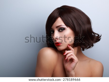 Beautiful makeup woman with short hairstyle and red nails gloss with empty copy space on blue background - stock photo