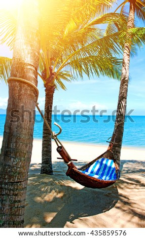 Beautiful Maldive beach and hammock. Empty hammock between palms at sandy beach. Summer holiday and vacation concept.