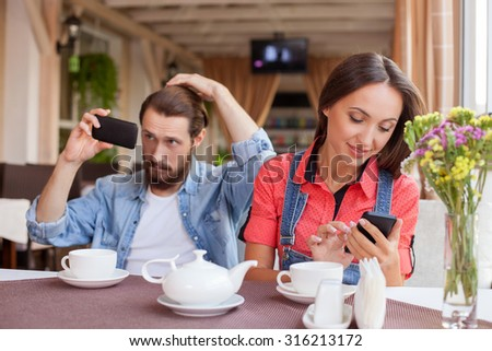 Beautiful man and woman are dating in cafeteria and drinking tea. The girl is holding a mobile phone and messaging. She is smiling. Her boyfriend is using a telephone as the mirror with joy - stock photo