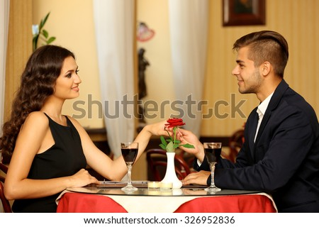 beautiful man and woman are flirting at the restaurant - stock photo