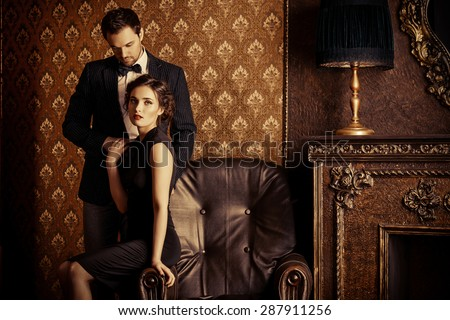 Beautiful man and woman in elegant evening clothes in classic vintage apartments. Glamour, fashion. Love concept. - stock photo