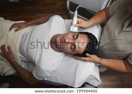 Beautiful man in white t-shirt having a laser skin treatment in a skincare clinic, male patient on the rejuvenation procedure in aesthetic clinic, laser procedure - stock photo