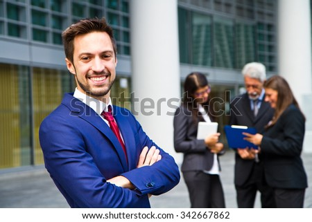 Beautiful man on the background of business people  - stock photo