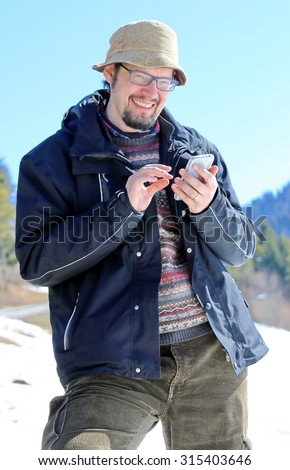 Beautiful man with Hat and mobile phone during the winter holidays in the mountains