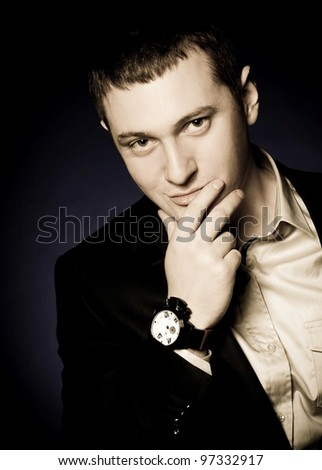 Beautiful man with watch on a dark background - stock photo