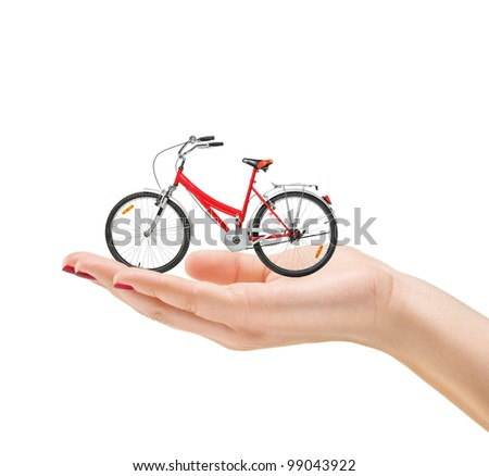 Beautiful manicured female hand holding a bike isolated on white background