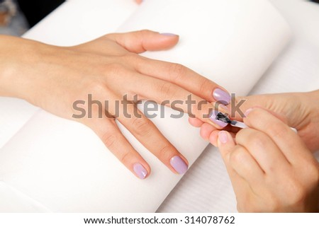 Beautiful manicured woman's nails with violet nail polish on soft white towel. - stock photo
