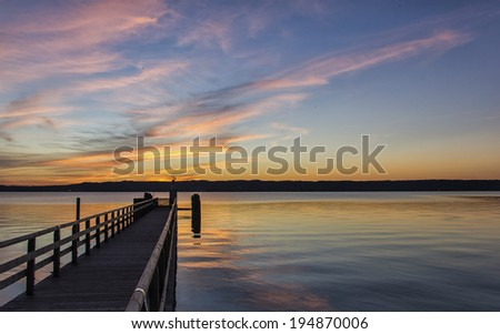 Beautiful marine sunset over a pier or jetty tinting the clouds a delicate pink and gold above a tranquil ocean - stock photo