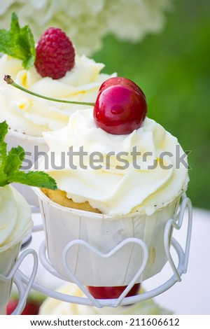 Beautiful mascarpone cupcakes with a cherry and a raspberry on top - stock photo