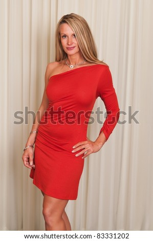 Beautiful mature blonde in a red dress - stock photo