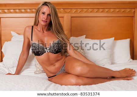 Beautiful mature blonde in bed in brown lingerie