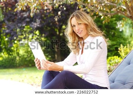 Beautiful mature business woman holding digital tablet while working at garden at home.  - stock photo