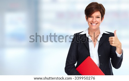 Beautiful mature business woman over blue office background.