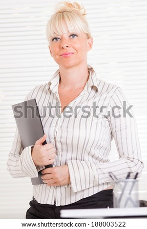 Beautiful mature Business woman standing in the office with document