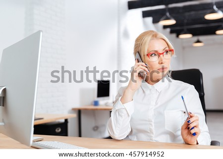 Beautiful mature business woman talking on phone in the office - stock photo