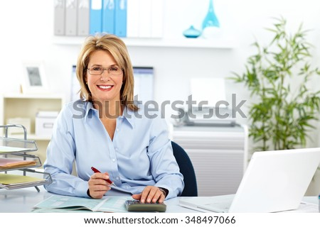 Beautiful mature business woman working in modern office. - stock photo