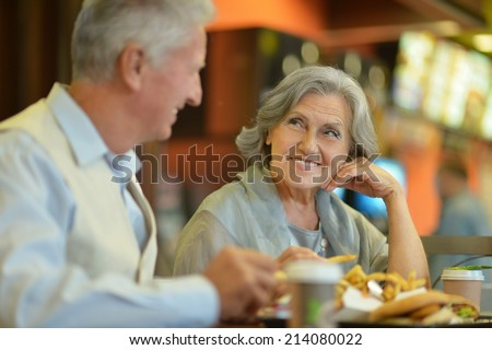 Beautiful mature couple eating french fries in cafe