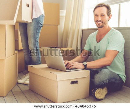 Beautiful mature couple is moving. Handsome mature man is using a laptop, looking at camera and smiling while his wife is packing their stuff