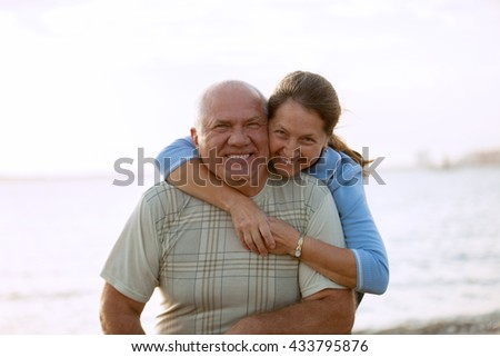 beautiful mature couple on  beach near  sea during sunset.
