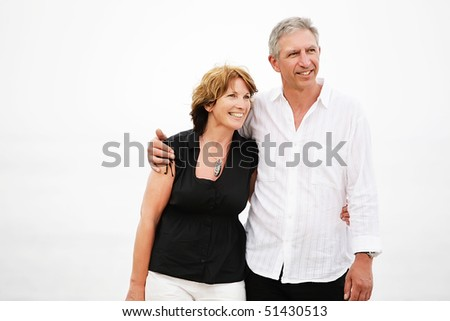 Beautiful mature couple taking a romantic walk. Shallow DoF with focus on the woman. - stock photo