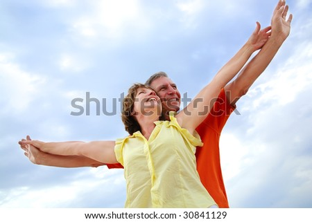 beautiful mature couple with arms outstretched