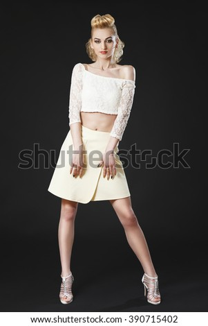 Beautiful mature girl posing in white top and skirt on black background, wearing high heels - stock photo