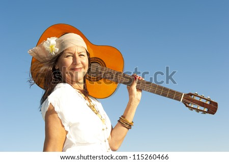 Beautiful mature hippie woman happy relaxed smiling and posing with  guitar, isolated with flower in hair, blue sky and lake as background and copy space. - stock photo