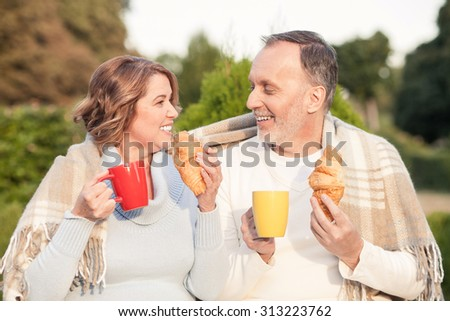 Beautiful mature husband and wife are resting in park. They are drinking hot coffee and eating tasty pastry. The man and woman are looking at each other and smiling