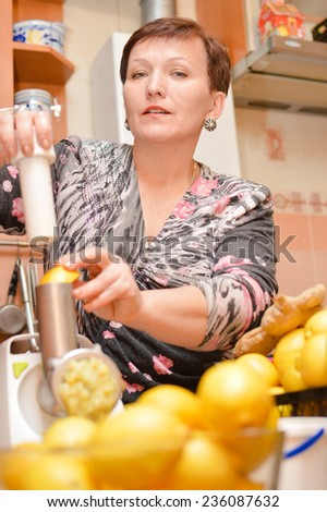 beautiful mature lady making organic healthy food using lemon, honey & ginger as ingredients & looking at camera