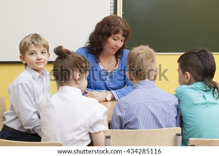 beautiful mature primary school teacher and four students read the book. Cute caucasian boy looks at the camera and smiling. Horizontal color image. - stock photo