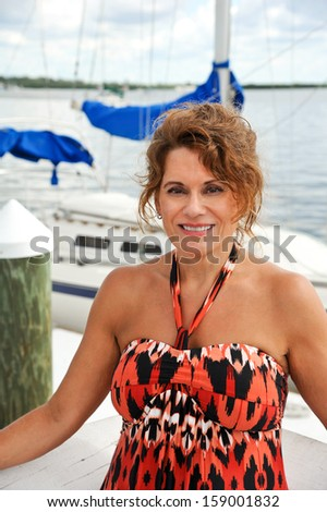 Beautiful Mature Woman at Marina in Front of a Sail Boat - stock photo