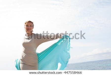 Beautiful mature woman by blue sea looking and smiling raising a floating fabric with her arms on a sunny holiday destination, outdoors. Senior active healthy woman enjoying the sun, lifestyle. - stock photo