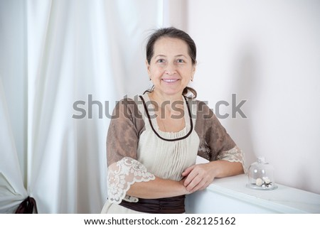 beautiful mature woman in a white room.  - stock photo