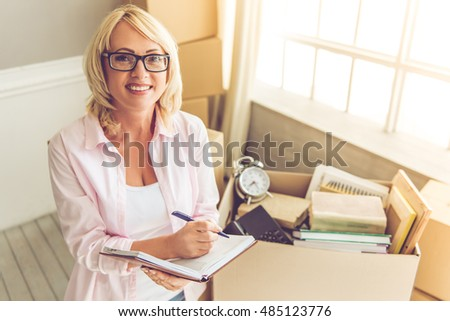 Beautiful mature woman in casual clothes is packing her stuff into the boxes, making notes, looking at camera and smiling while moving to the new apartment
