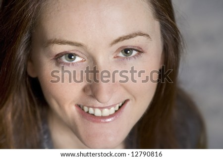 Beautiful mature woman in grey on a grey background - stock photo