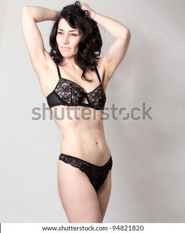Beautiful mature woman in lingerie posing in studio - stock photo