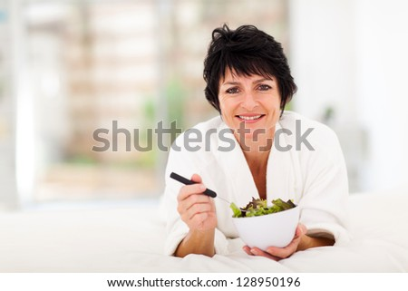 beautiful mature woman lying on bed and eating green salad