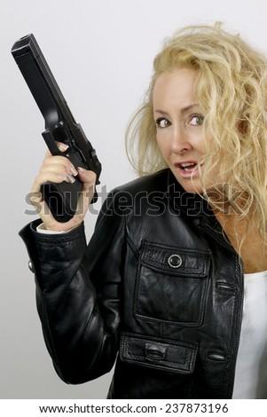beautiful mature woman posing with a gun - stock photo