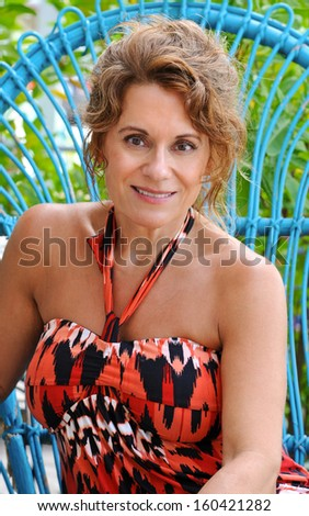 Beautiful Mature Woman Sitting in a Blue Wicker Chair  - stock photo