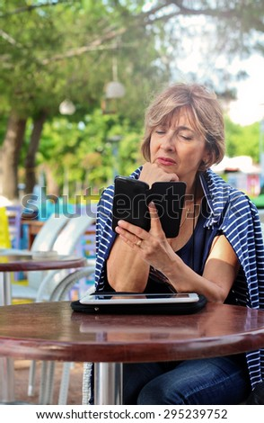 Beautiful mature woman sitting in the sidewalk cafe using a smart phone. - stock photo