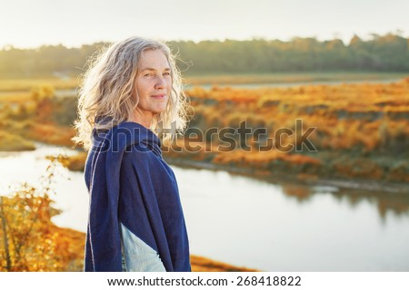 Beautiful mature woman standing in front of the river in autumn - stock photo
