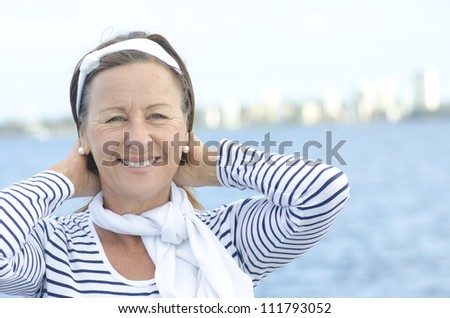 Beautiful mature woman standing relaxed at seaside, looking confident and happy, isolated with sky  and water as background and copy space. - stock photo