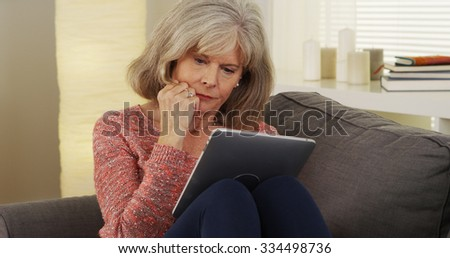 Beautiful mature woman tablet reading - stock photo