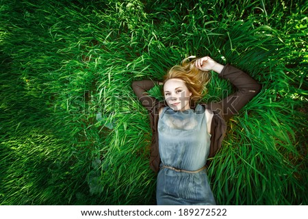 Beautiful meditative young woman lying in the grass. Summer, freedom concept. Blonde hair. Small amount of grain added for best final impression. - stock photo