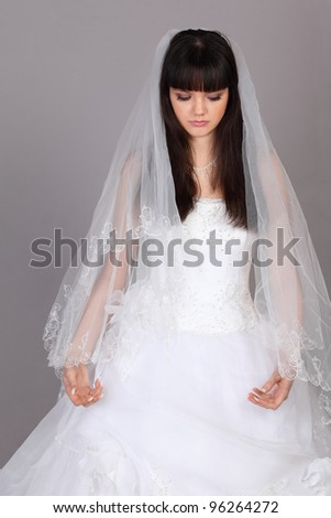 Beautiful melancholy bride dressed in white dress look down on gray background - stock photo