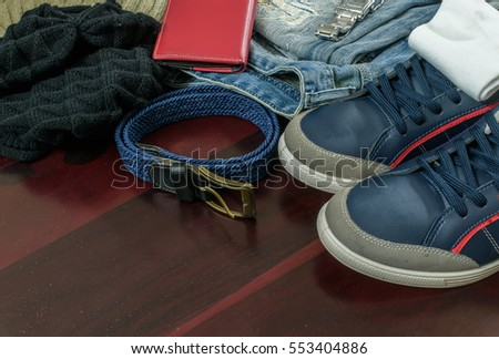 Beautiful men fashion with Sweater woolen cap Jeans Belt Socks Wallet Watch and blue shoes on wooden background.